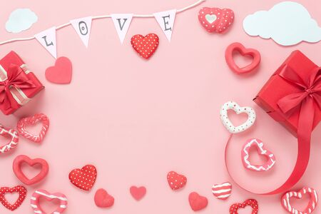 Table top view image of decoration valentines day background concept.Flat lay arrangement of red shape & gift box with essential items on modern rustic pink paper with middle space for mock up design