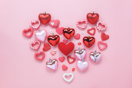 Table top view aerial image of sign valentines day background concept.Flat lay arrangement colorful many heart shape on modern grunge pink paper at home office desk studio.Pastel tone design backdrop. Stock Photo