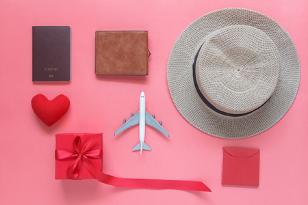 Passport and clothes with many items in holiday season on pink paper.