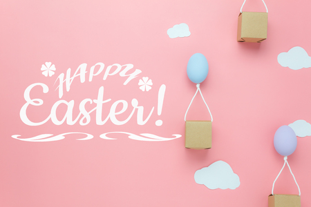 Top view shot of arrangement decoration Happy Easter holiday background concept.Flat lay colorful Easter egg balloon fly transfer gift box on sky pink paper with cloud.Text design with pastel tone.