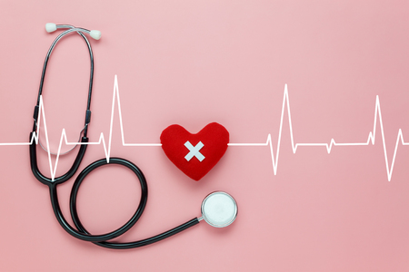 Table top view aerial image of accessories healthcare & medical background concept.Red heart & stethoscope with design heart wave on pink paper.Flat lay of idea for doctor treat patient in hospital.