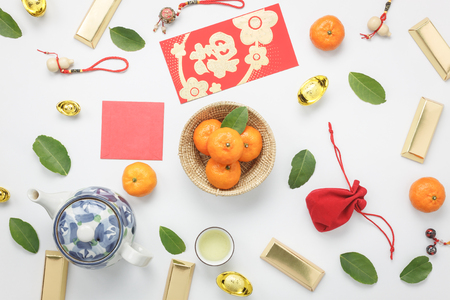 Top view aerial image shot of arrangement decoration Chinese new year & lunar new year holiday background concept.Flat lay fresh orange with food & drink on modern white wooden at home office desk.