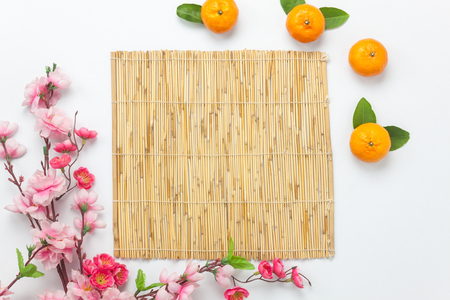 Flat lay aerial image of accessories Lunar vacation & Chinese New Year holiday background concept.Bamboo floor of space for mock up & template.Top view orange & flower on white wood at office desk.