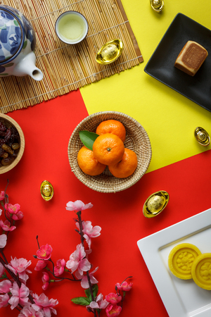 Top view aerial image of arrangement decoration Chinese new year & lunar holiday background concept.Flat lay fresh orange with food & drink on modern red & yellow paper at office desk.Pastel tone. Stock Photo