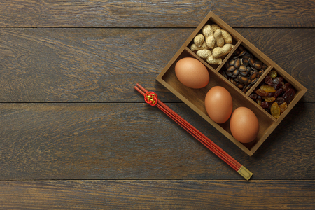 Top view aerial image shot of arrangement decoration Chinese new year & lunar holiday background concept.Flat lay food and essential items on modern brown wooden at home office desk.Space for creative