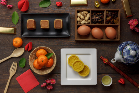Top view aerial image shot of arrangement decoration Chinese new year & lunar new year holiday background concept.Flat lay fresh orange with food & drink on modern brown wooden at home office desk.