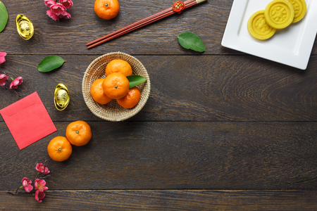 Top view shot of arrangement decoration Chinese new year & lunar holiday background concept.Flat lay orange & dessert also red pocket money on modern brown wooden at home desk.Free space for mock up.