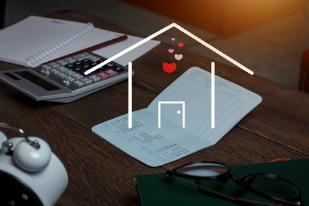 Business & Finance background concept.Home on banking for savings or investment on modern rustic brown wooden at home office desk.Essential objects for working.dark tone.copy space.