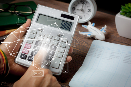 Business or finance background concept.Close up man calculate payment or money for plan to travel all world with saving banking on modern rustic brown office desk.Idea for traveler for global trip. Stock Photo