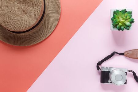 Table top view accessory of clothing women plan to travel in holiday background.Beauty & Fashion concept.Flat lay of camera with many essential items hat and green plant on orange & pink pastel paper.