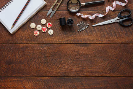 Top view aerial image fashion designer background concept.Flat lay sewing accessory or tailor tool work shop on modern rustic brown wooden at home office desk studio.Space for creative design mock up.