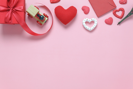 Table top view aerial image of sign valentines day background concept.Flat lay many heart shape with decorations and gift box on modern pink paper at home office desk studio.Pastel tone design.
