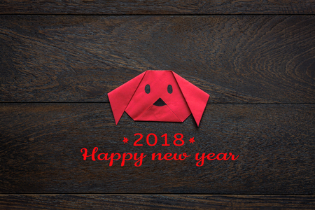 Top view shot of arrangement decoration Chinese new year & lunar holiday background concept.Flat lay of red dog paper craft by handmade on modern brown wooden at home desk.Text for 2018 design season.