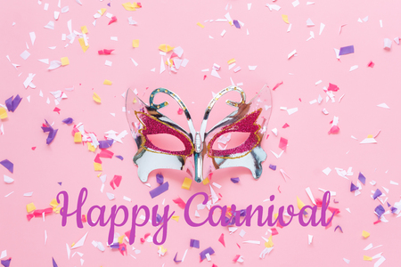Table top view aerial image of beautiful colorful carnival mask or photo booth prop background.Flat lay object on modern rustic pink wallpaper at  office desk studio.space for creative design mock up. Stock Photo