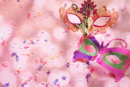 Table top view aerial image of beautiful couple carnival mask background.Flat lay essential accessory on modern rustic pink wallpaper at home office desk studio. Copy space for creative design text. Stock Photo