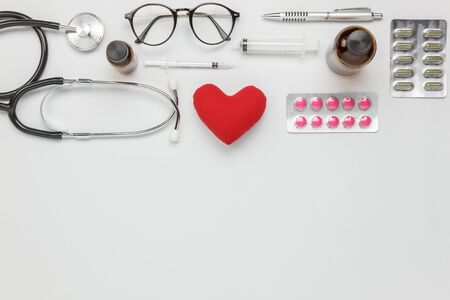 Table top view aerial image of accessories healthcare & medical background concept.Red heart & stethoscope and equipment tools on white paper.Flat lay essential items for doctor using treat patient.