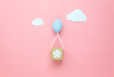 Top view shot of arrangement decoration Happy Easter holiday background concept.Flat lay minimal colorful Easter egg balloon flying transfer gift box on modern pink paper at office desk.pastel tone.