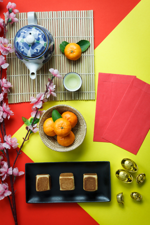 Top view aerial image of arrangement decoration Chinese new year & lunar holiday background concept.Flat lay fresh orange with food & beverage on modern red & yellow paper at office desk.Pastel tone.
