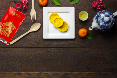 Top view aerial image decoration Chinese new year & lunar new year holiday background concept.Flat lay dessert and fresh orange with food & drink on modern brown wooden at home office desk.copy space.
