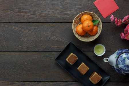 Top view shot of arrangement decoration Chinese new year & lunar holiday background concept.Flat lay orange & dessert & food with beverage also red pocket money on modern brown wooden at home desk.