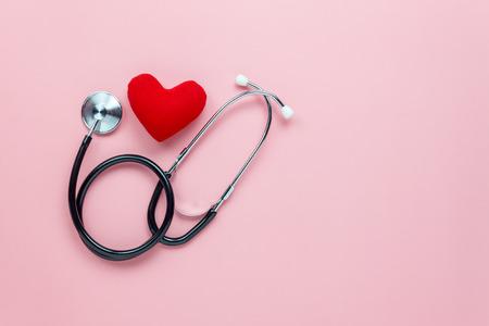 Tischplatteansichtvogelperspektive des Zubehörgesundheitswesens u. Des medizinischen Hintergrundkonzeptes Rotes Herz u. Stethoskop mit copyspace auf rosa Papier Flache Lage der Idee für Doktorfestlichkeitspatienten im Krankenhaus. Standard-Bild