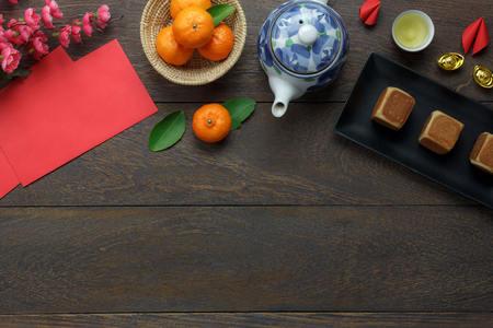 Table top view aerial image of decorations Happy Chinese New Year & Lunar festival holiday background concept.Flat lay food & drink on modern rustic brown wooden at home office desk studio.copy space.