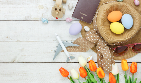 Table top view shot of decoration Happy Easter holiday background with accessory woman to travel concept.Flat lay bunny egg with tulip flower and rabbit doll on modern white wooden at office desk. Stock Photo