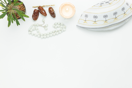 Table top view aerial image of decoration Ramadan Kareem holiday background.Flat lay essential items date with white rosary & lighting and hat Islamic is on modern rustic white wooden at office desk.