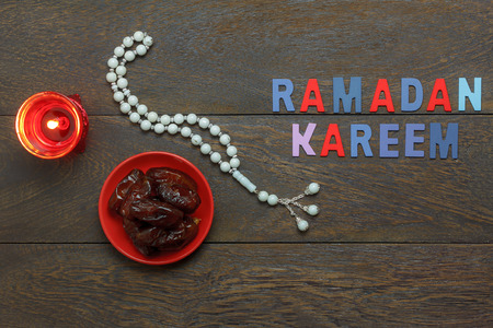 Table top view aerial image of decoration Ramadan Kareem holiday background.Flat lay date in red plate with white rosary & lighting.The text invitation season on modern  brown wood at office desk.