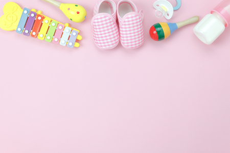 Table top view decoration kid toys for develop background concept.Flat lay baby shoes with items child on modern pink paper at office desk.Copy space for add text.Creative deign pastel tone wallpaper. Stock Photo