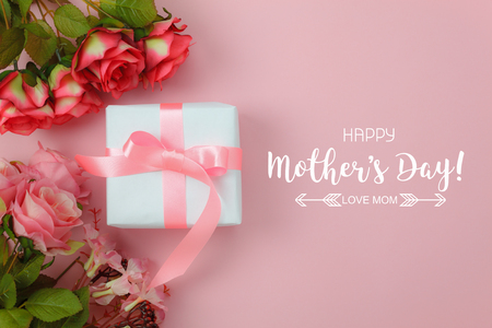 Top view aerial image of decoration Happy mothers day holiday background concept.Flat lay white gift box with red rose on modern beautiful pink paper at home office desk.Free space for design text. Stock Photo
