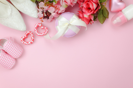 Top view aerial image of decoration Happy mothers day holiday background concept.Flat lay accessory objects the pink rose with clothing woman & kid and child toys  on pink paper at home office desk. Stock Photo