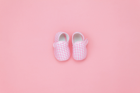 Table top view aerial image of decorations clothing fashion for kids background concept.Flat lay essential object the baby shoes for newborn on modern rustic pink paper at home office desk.pastel tone