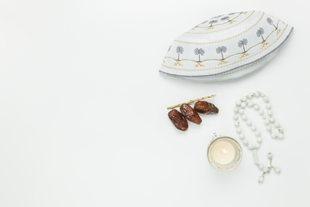 Table top view aerial image of decoration Ramadan Kareem holiday background.Flat lay dates with rosary & lighting and holy hat.The essential objects on modern rustic white wooden at office desk.