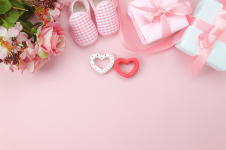 Top view aerial image of decorations Happy mothers day holiday background concept.Flat lay essential objects the pink rose with clothing woman & kid and child toys on pink paper at home office desk.