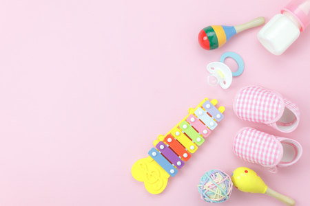 Table top view kids toys for develop background concept.Flat lay object the colorful wooden ball & percussion musical instruments on modern paper pink at office desk.Design pastel tone with copy space