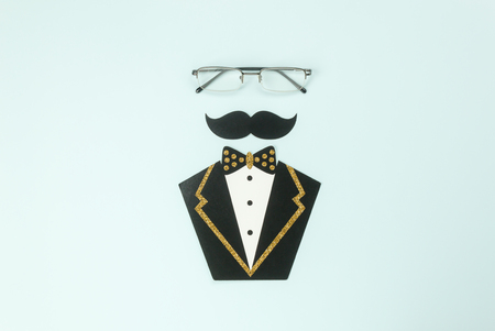 Table top view Happy Fathers day holiday background concept.Flat lay glasses & mustache and suit gentleman.accessories objects on modern rustic blue paper at home office desk.space creative design.