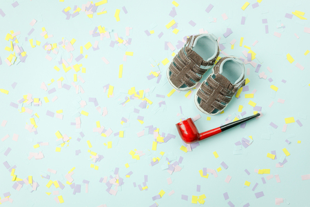 Table top view Happy Fathers day holiday background concept.Flat lay accessories objects sign of season.Baby shoes with pipe smoking on modern rustic blue paper at office desk.space creative design.