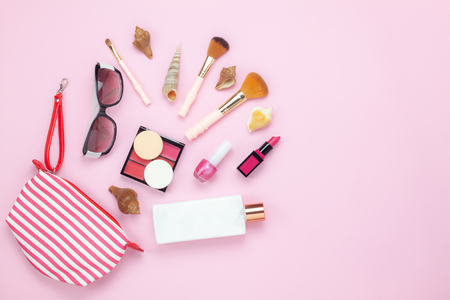 Table top view women fashion & beauty for travel summer holiday background concept.Flat lay accessories objects sun glasses & sun block body lotion on modern rustic pink paper wallpaper and copy space