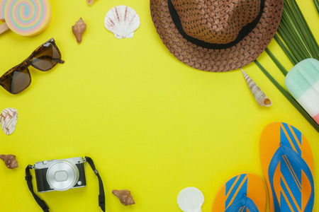 Table top view aerial image of fashion tor travel in summer holiday background.Flat lay accessories clothing for traveler on modern rustic yellow paper at office desk.Free space for creative design.