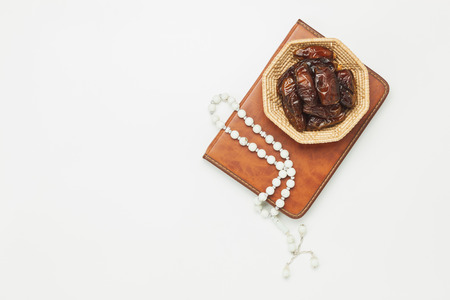 Table top view aerial image of decoration Ramadan Kareem holiday background.Flat lay date in wood basket with white rosary & lighting.The holy book of Koran on modern rustic white wood at office desk.