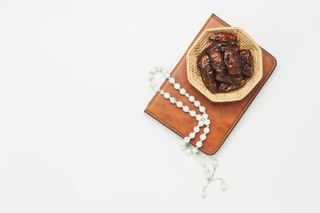 桌子顶视图航空图像装饰斋月Kareem节日背景。扁枣木篮子与白色念珠和照明。《古兰经》在现代乡村白色的木头上放在办公桌上。