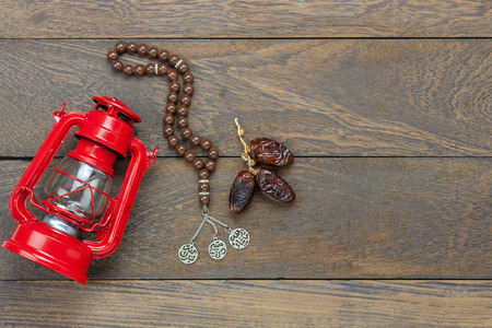 Table top view aerial image of decoration Ramadan Kareem holiday background.Flat lay date & rosary and red vintage lighting on modern rustic brown wooden at office desk. Stock Photo