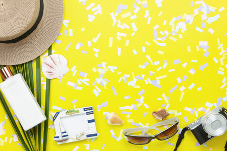 Table top view aerial image of items to travel summer beach holiday background concept.Flat lay essentials accessories for travel to beach trip.Fashion sun glasses with camera & hat on yellow paper. Stock Photo