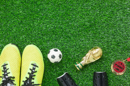 Table top view aerial image soccer or football season background.Flat lay accessories trophy & ball with shoe and medal on the artificial green grass wallpaper.Free space for design text and content. Stock Photo