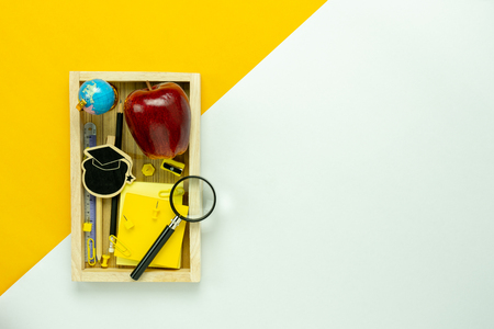 Table top view aerial image of decorations education for back to school background concept.Flat lay of variety objects apple & stationary with wood shelf on modern  paper duo tone white and yellow. Stock Photo