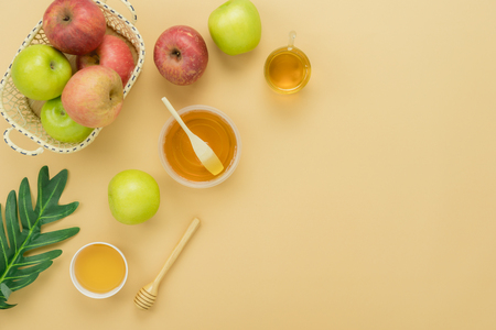 Table top view aerial image of decorations Jewish holiday Rosh Hashana background concept.Flat lay of variety apple & honey with green leave on modern rustic yellow paper.Free space for design text. Stock Photo