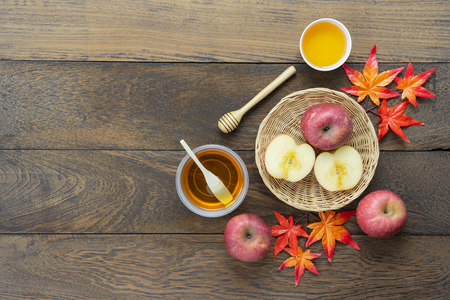 Table top view aerial image of decoration Fall harvest or Rosh Hashanah day background concept.Flat lay apple slice & honey bee with maple leave on modern rustic brown wooden.Copy space for add text.