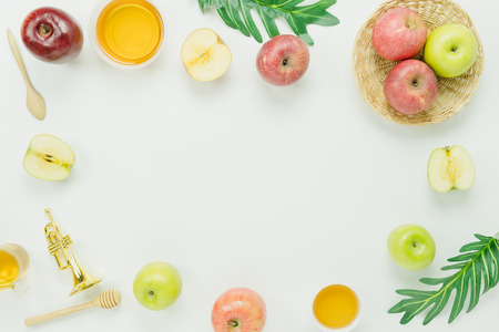 Table top view aerial image of decorations Jewish holiday Rosh Hashana banner background concept.Flat lay of variety  apple & honey with green leave on modern rustic white wooden.Free space for design