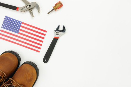 Table top view aerial image of decoration the sign of USA labor day on Sep 3,2018 background concept. Flat lay accessories tools and US flag and clothing for worker on modern rustic white wooden.